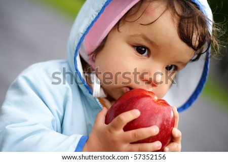 portrait of the beautiful child holding an apple
