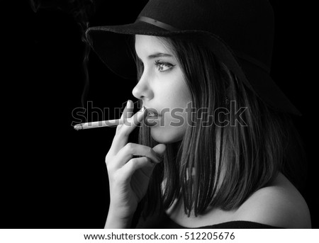 Portrait of the beautiful elegant girl smoking cigarette isolated on black background.