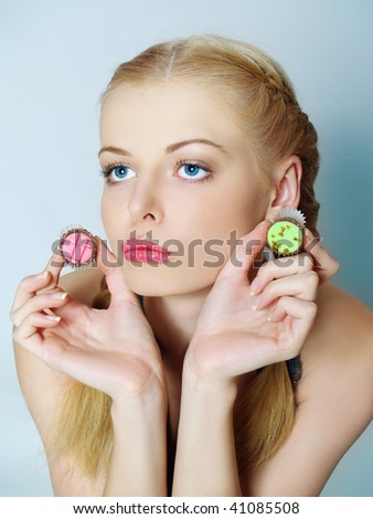 Portrait of the beautiful girl choosing between two sweets