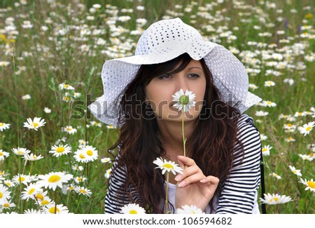 Portrait of the beautiful girl in a natural environment in white hat - stock photo