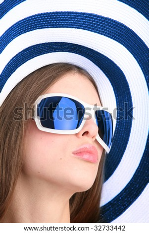 portrait of the beautiful girl in sunglasses and striped hat - stock photo