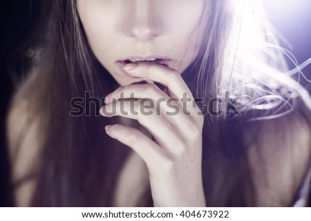 portrait of the beautiful girl in the light of a searchlight. Shooting in studio - stock photo