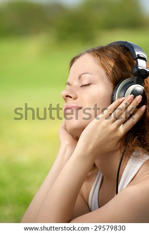 Portrait of the beautiful girl listening to music in ear-phones in park - stock photo