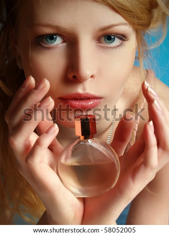 Portrait of the beautiful girl with a bottle of perfume in her hands - stock photo