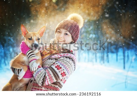 Portrait of the beautiful girl with a dog in the winter wood - stock photo