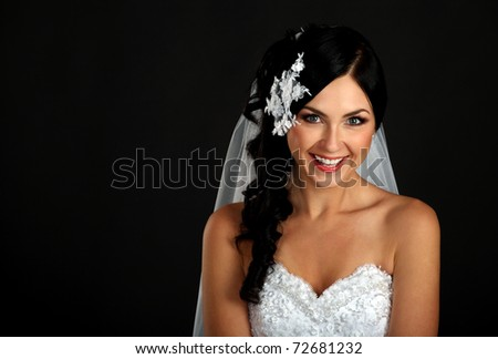 Portrait of the beautiful happy bride on a dark background - stock photo