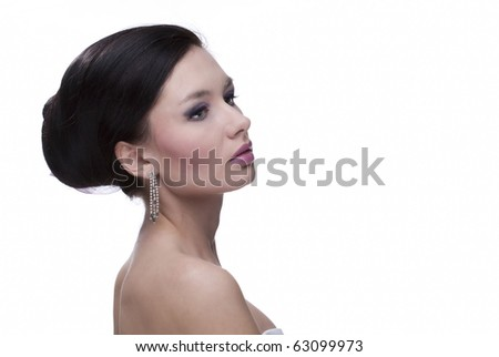 Portrait of the beautiful, sensual, young caucasian black-haired woman with silver earrings and blue and violet flower in her hair, on white isolated, a lot of copyspace and textspace - stock photo