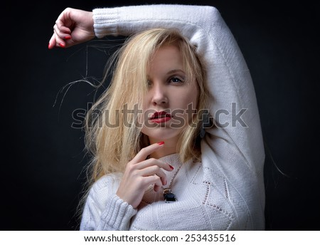 Portrait of the beautiful sexy blonde woman, She is posing in studio with dark background. - stock photo