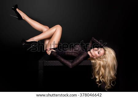 Portrait of the beautiful sexy blonde woman with long legs and amazing volume hair, long eyelashes and perfect face in a black dress and shapely, smooth and tanned legs and high heels - stock photo