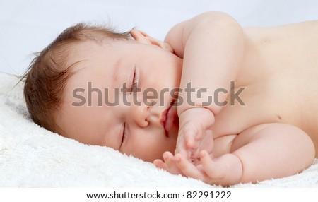 Portrait of the beautiful small sleeping baby - stock photo