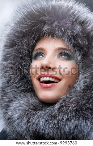 Portrait of the beautiful, smiling young woman with a fur hood. - stock photo