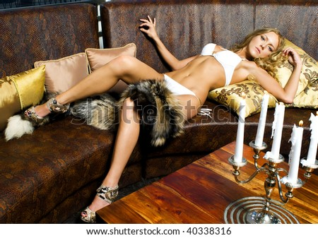 Portrait of the beautiful woman in beachwear. She is lying on the leather sofa - stock photo