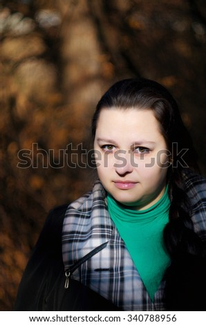 Portrait of the beautiful woman on walk in park in solar autumn day. - stock photo