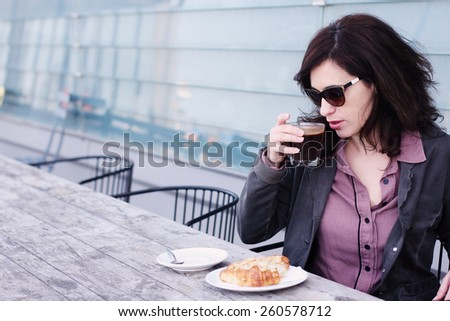 Portrait of the beautiful woman sitting in the cafe - stock photo
