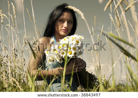 Portrait of the beautiful woman with bunch of camomiles