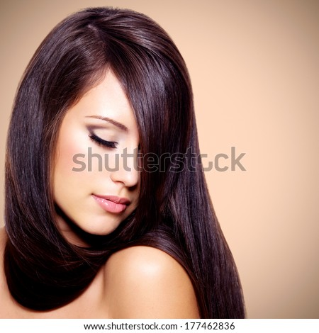 Portrait of the beautiful woman with long brown hair posing at studio