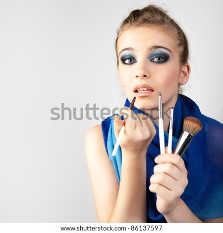 Portrait of the beautiful woman with make-up brushes near attractive face. Girl lipstick. - stock photo