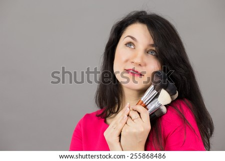 Portrait of the beautiful woman with makeup brushes near face
