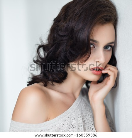 Portrait of the beautiful young fashionable girl with brown hair in studio posing against a white wall