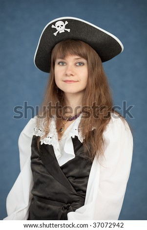 Portrait of the beautiful young girl in a pirate hat on blue background