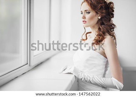 Portrait of the beautiful young girl in wedding dress at the window - stock photo