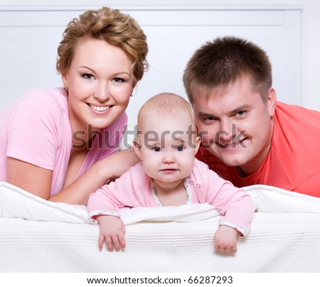 Portrait of the Beautiful young happy family lying in bed at home - stock photo