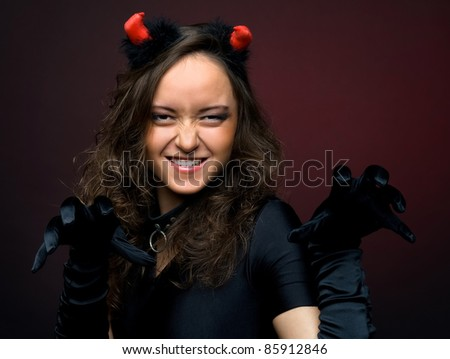 Portrait of the beautiful young woman in devil carnival shape - stock photo