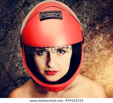 Portrait of the beautiful young woman parachutist with red lips in red helmet on stone background