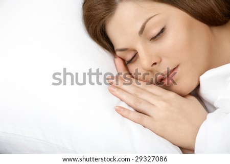 Portrait of the beautiful young woman sleeping in white bed - stock photo