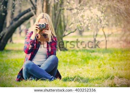 portrait of the beautiful young woman with camera sitting near blooming cherry