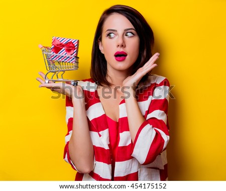portrait of the beautiful young woman with cart and gift on the yellow background