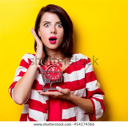 portrait of the beautiful young woman with cart for shopping and red alarm clock on the yellow background - stock photo
