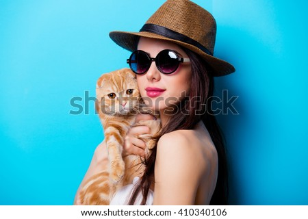portrait of the beautiful young woman with cat on the blue background - stock photo