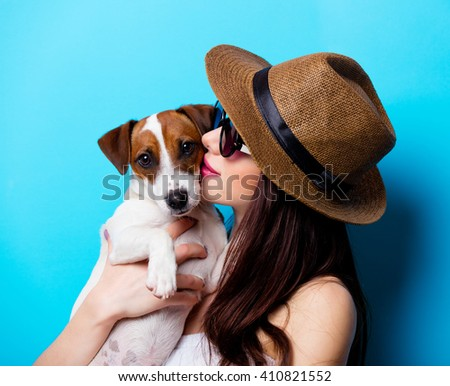portrait of the beautiful young woman with dog on the blue background - stock photo
