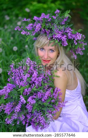 Portrait of the beautiful young woman with flowers - stock photo