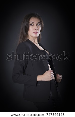 Portrait of the beautiful young woman with long black hair posing standing over dark background