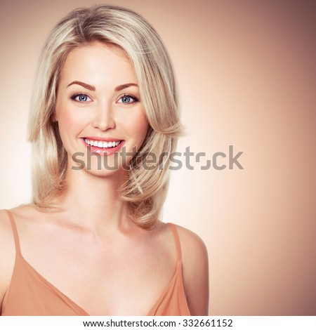 Portrait of the beautiful young woman with smile looking at camera - stock photo