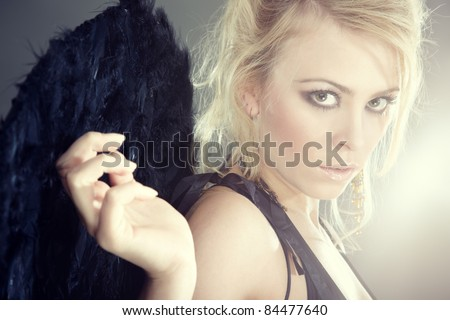 Portrait of the blond female angel with artificial wings - stock photo