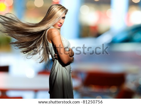 Portrait of the blonde with  flyaway hair in the background of city - stock photo