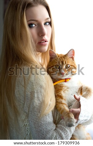 Portrait of the blonde woman with cat near window - stock photo