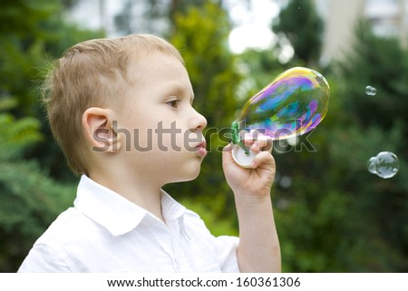 Portrait of the boy inflating soap bubbles outdoors - stock photo