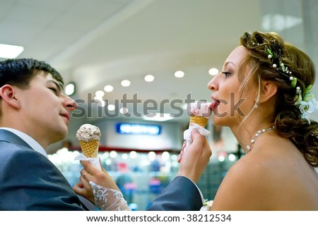 Portrait of the bride and groom with ice-cream. Shallow DOF - stock photo