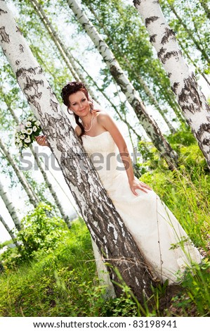 Portrait of the bride in park in the summer sunny day - stock photo