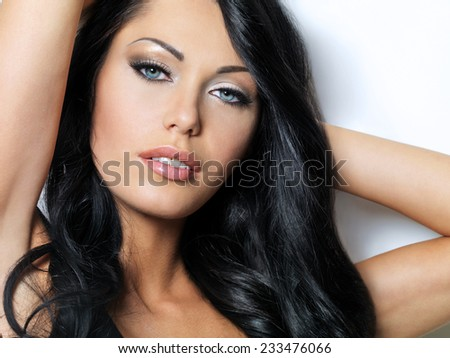 Portrait of the brunette woman with beautiful blue eyes - posing at studio - stock photo