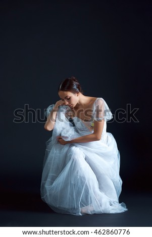 Portrait of the classical ballerina in white dress on the black background