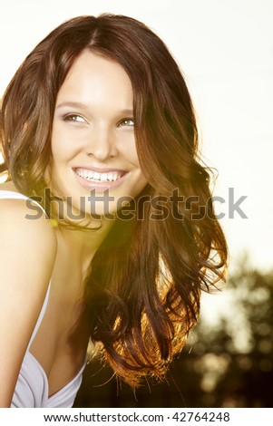 Portrait of the curly beautiful woman in sunlight beams - stock photo
