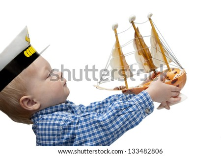 Portrait of the cute child  with the model ship - stock photo