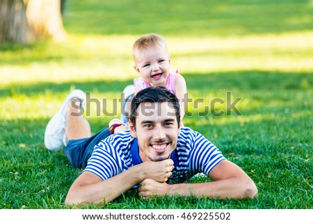 portrait of the cute toddler and her father on the grass in the park