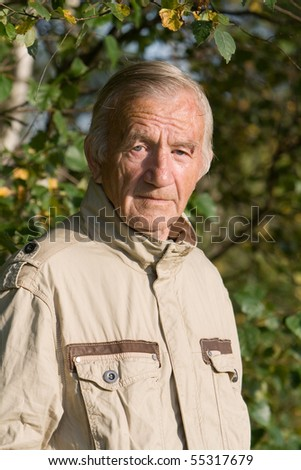 Portrait of the elderly man in a beige jacket in village on the nature