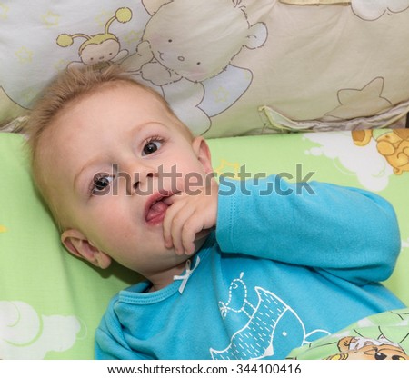 Portrait of the fair-haired thought kid lying in a bed and sucking a finger - stock photo